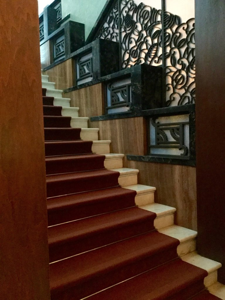 Stairs leading to the second floor. Marble steps edged by intricate metalwork and zigzag handrails.